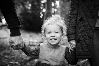 Young girl happy and holding mum and dad's hands and grinning, black and white family photographer in Beckenham