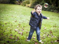 Natural photograph of boy chasing bubbles in the park and having fun running around, lifestyle image taken in Beckenham
