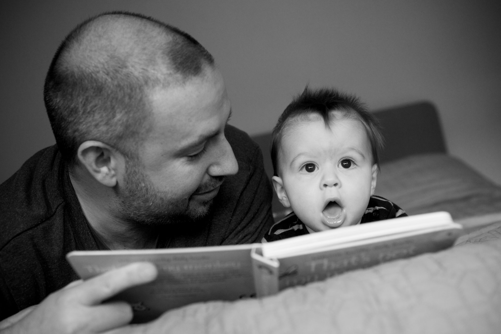 Baby reading book with Daddy on the bed in baby photoshoot in Bromley
