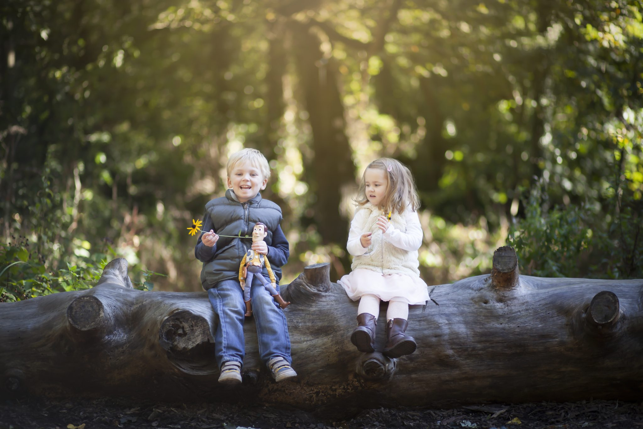 Portrait of Boy and girl sitting on a log dangling their legs and holding flowers in a Beckenham park in Autumn