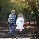 Natural family photo of brother and sister holding hands and walking outside in a Beckenham park on a cold Autumn day