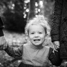 Natural black and white lifestyle image of young girl holding her parents hands and smiling in a local park called Kelesy Park in Beckenham Kent
