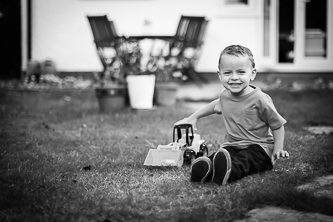 Lifestyle image of young boy playing with his truck in his back garden at his home, black and white photography at home in Beckenham