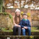 Portrait of a boy and girl sitting on the wall smiling in the winter park, photographed outside in Beckenham Place Park