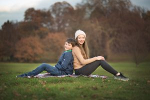 Family photograph of older brother and sister relaxing on a rug on location in their local park in winter time in Beckenham