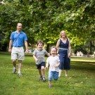Family having fun and racing each other across the grass in a park in Summer, photographed in West Wickham area