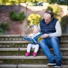 Photo of Dad and young daughter sitting on steps reading book, daughter looking lovingly into Dad's eyes in Beckenham, a lovely natural family moment captured