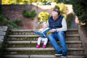 Family photo of Dad and young daughter sitting on steps reading book in Beckenham, daughter looking lovingly into Dad's eyes in Beckenham, a lovely natural family moment captured