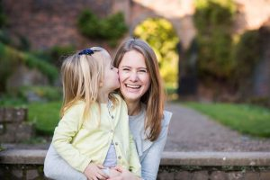 Natural picture of mum being kissed by daughter on the cheek at Bromley family photoshoot, mum laughing and sitting on steps. Photographed in Beckenham Place Park