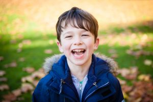Image of Young boy laughing outside, photoraphed in a park in Kent in the Autumn, natural Autumn colours all around him