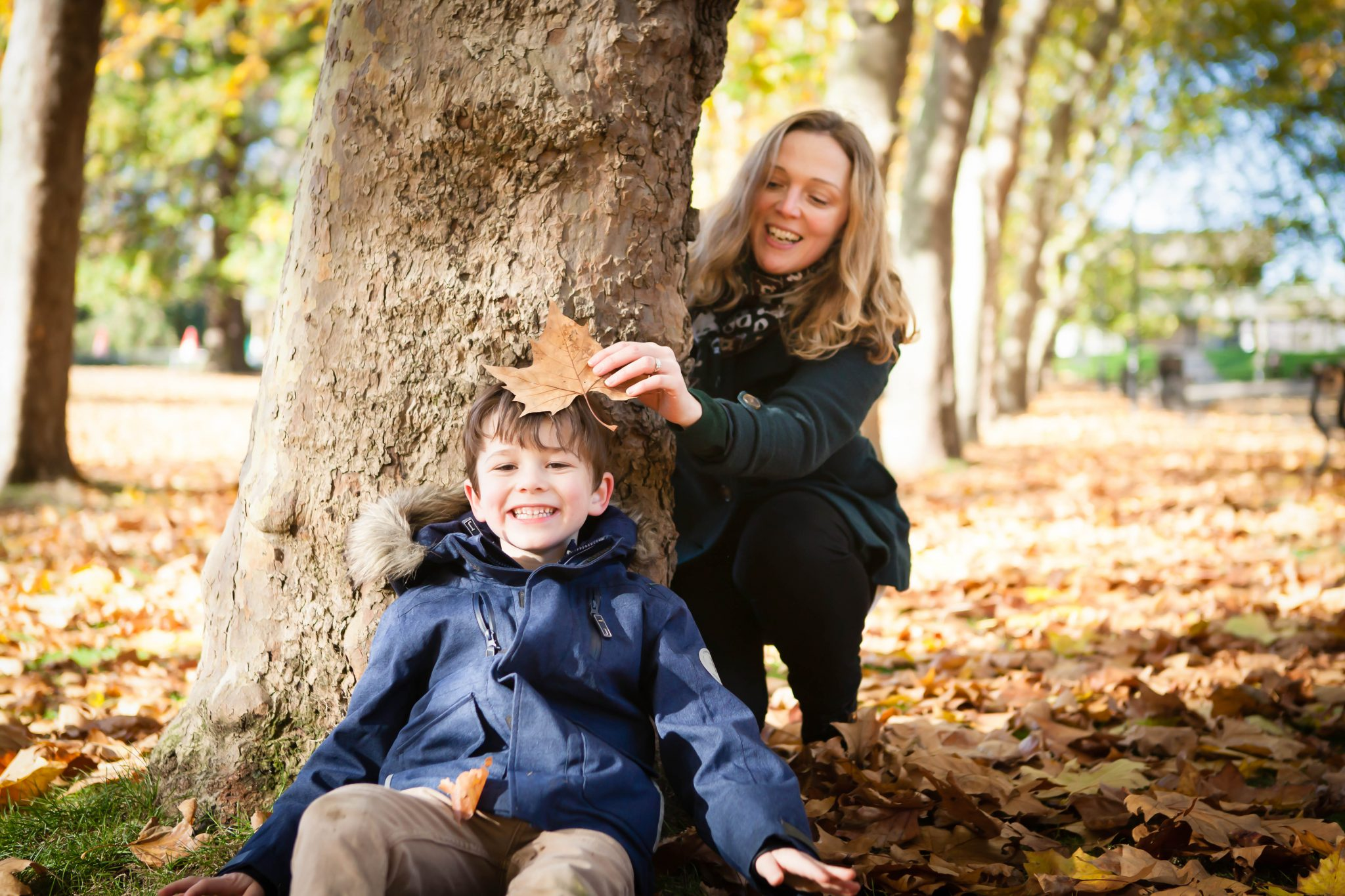 Family fun outside with mum and son photographed playing around a tree with leaves and playing hide and seek