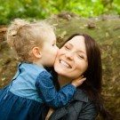 Image of daughter hugging mummy and kissing her on the cheek, natural photo of mum with her eyes closed grinning and having fun, photographed in Kelsey Park in Beckenham
