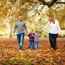 Photo of parents and young boys walking among the autumn leaves in Kelsey Park in Beckenham, all holding hands and smiling among the orange leaves