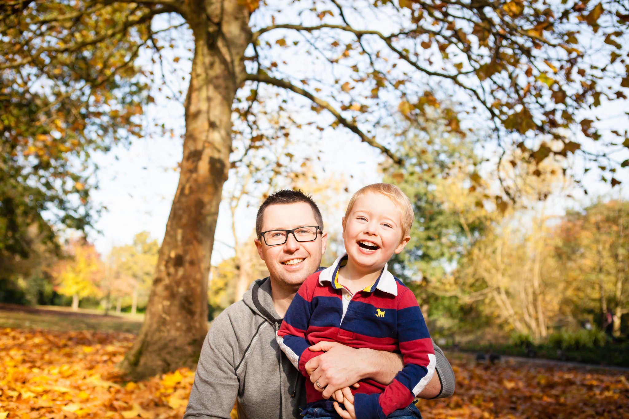 Autumn photography outside of dad and son laughing and cuddling, family fun and giggles in Beckenham