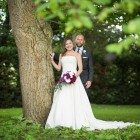 Bride and groom leaning by tree at Oaks Farm wedding venue, taken by Kent wedding photographer