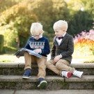 Lifestyle photography of two brothers reading a book together and relaxing on the steps in the gardens of Beckenham Place Park