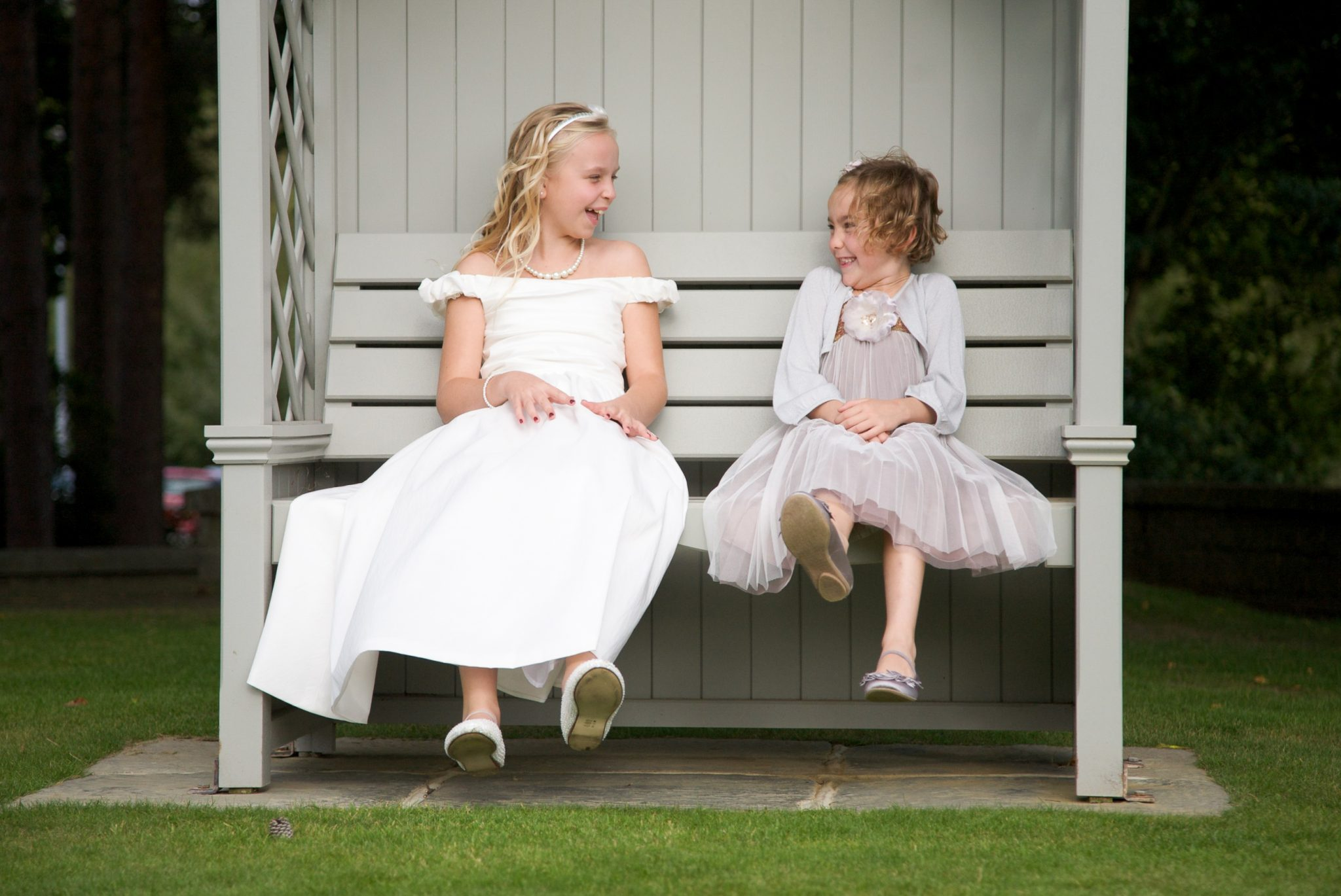 Bridesmaids giggling on bench at wedding taken by Bromley Wedding Photographer
