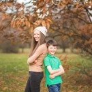Brother and sister leaning against each other under a tree of orange Autumn leaves, smiling and natural portrait of a family having fun in the West Wickham area