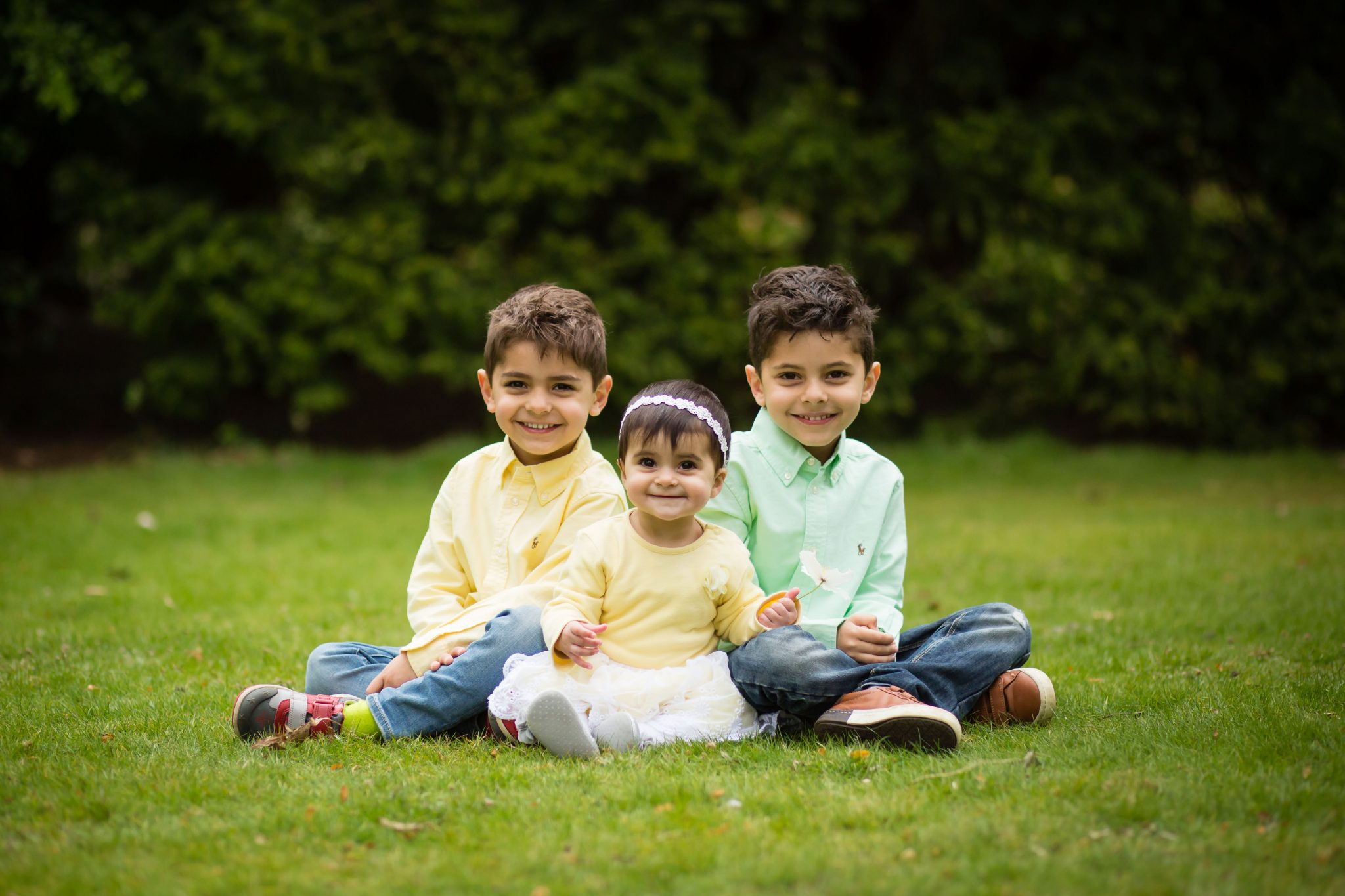 Brothers and sisters sat on the grass smiling with Bromley photographer