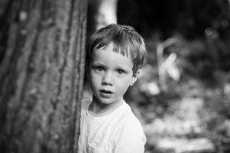 Young boy in black and white photo playing peek-a-boo behind a tree in Kelsey Park in Beckenham