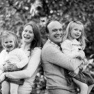Outdoor lifestyle photograph of Mum and dad and children laughing and having fun in the local park in Beckenham, black and white image with family all laughing in their first ever family shoot