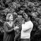 Photo of parents and son cuddling and laughing in a black and white image outside in the woods, natural family fun and giggles in Beckenham