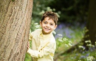 Photo of boy playing peek-a-boo behind tree and smiling cheekily in the park in Beckenham in the Spring