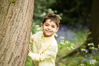 Photo of boy playing peek-a-boo behind tree and smiling cheekily in the park in South East London taken on family photoshoot