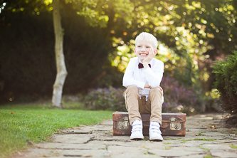 Outdoor portrait of young boy sitting on suitcase, elbow resting on his knee and smiling at his family, photographed in Beckenham