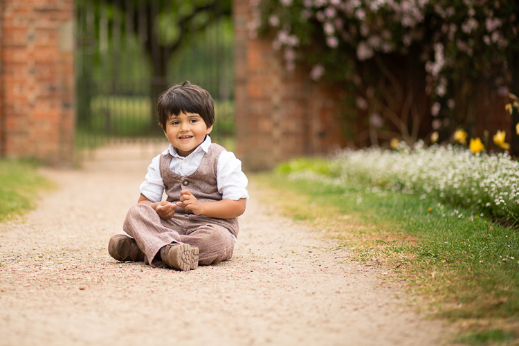 Portrait of a Boy sat on gravel path looking over at his family and smiling mischieviously