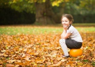 Girl sat on pumpkin in autumn leaves shown in an image by Beckenham photographer