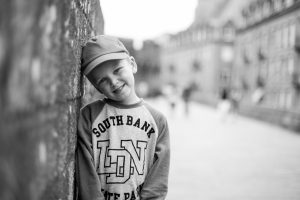 Holiday picture in France of young boy leaning against the wall