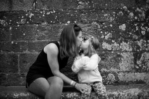Outdoor family picture in France of mum and daughter kissing