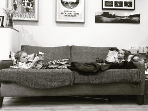 Natural image of brother and sister hanging out on sofa reading books