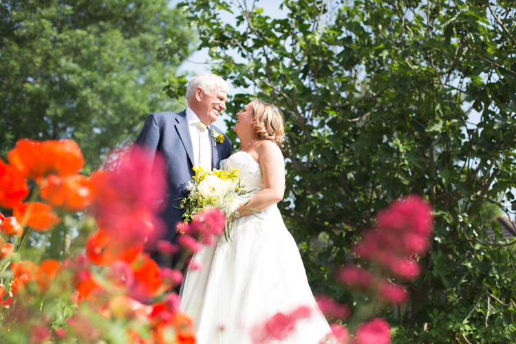 Bride and groom in front of flowers taken by wedding photographer in Bromley, Kent