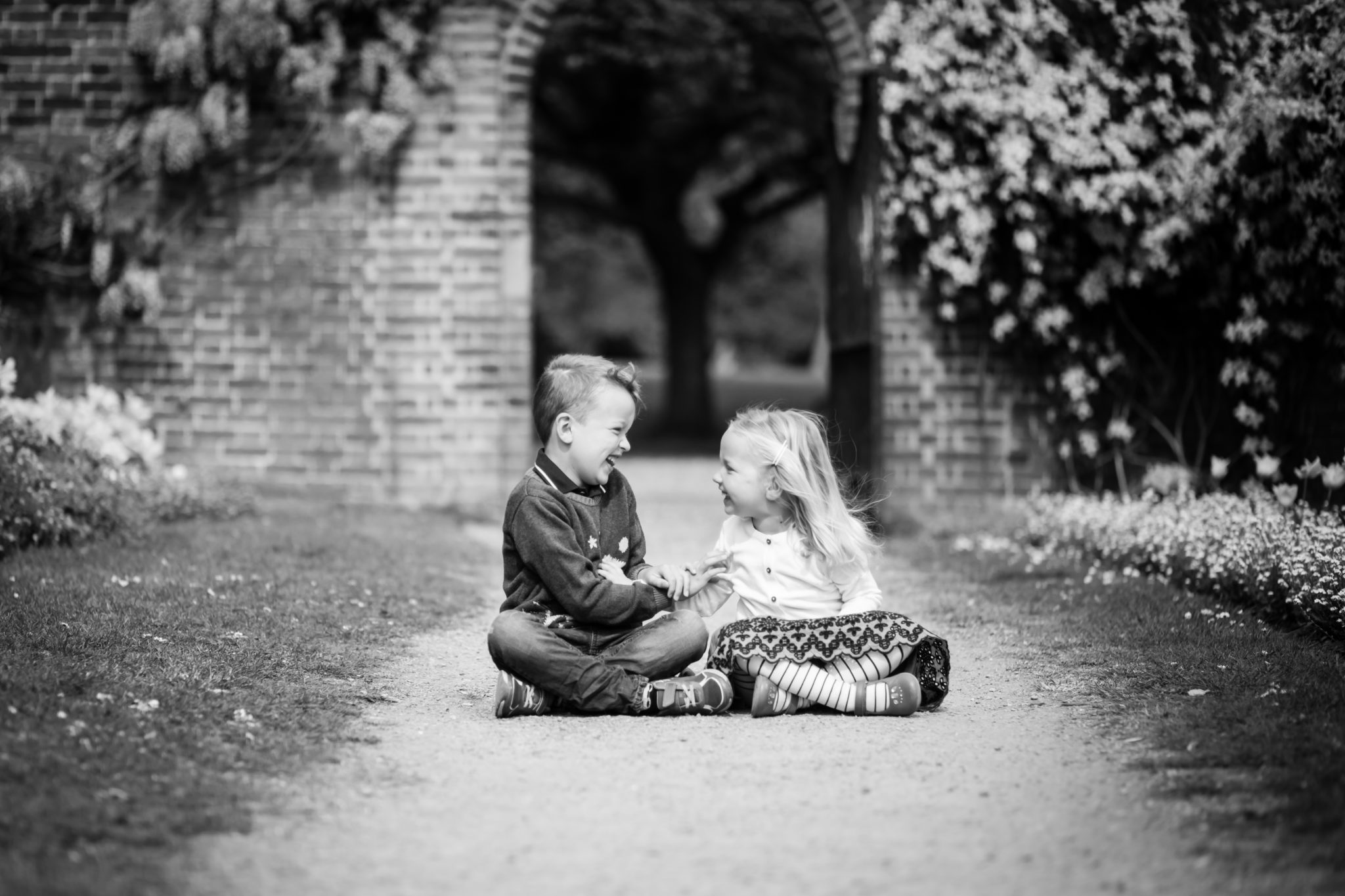 Brother and sister laughing in black and white family photo in Beckenham outdoor park