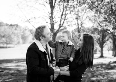 Son tickling dad's face on family photoshoot in London in Beckenham Place Park