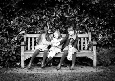 Sisters giggling and tickling each other on a bench in Kelsey Park and taken by Beckenham Photographer