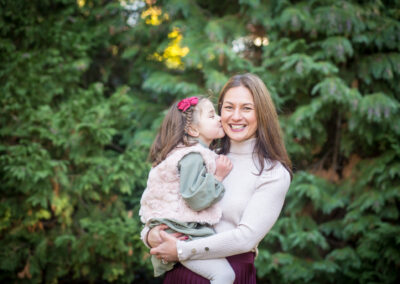 Daughter kissing mum on the cheek in Kelsey Park, Beckenham
