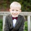 Children photography in Beckenham, boy smiling on a bench in local park