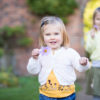 Girl holding flower in Beckenham Park from family photoshoot