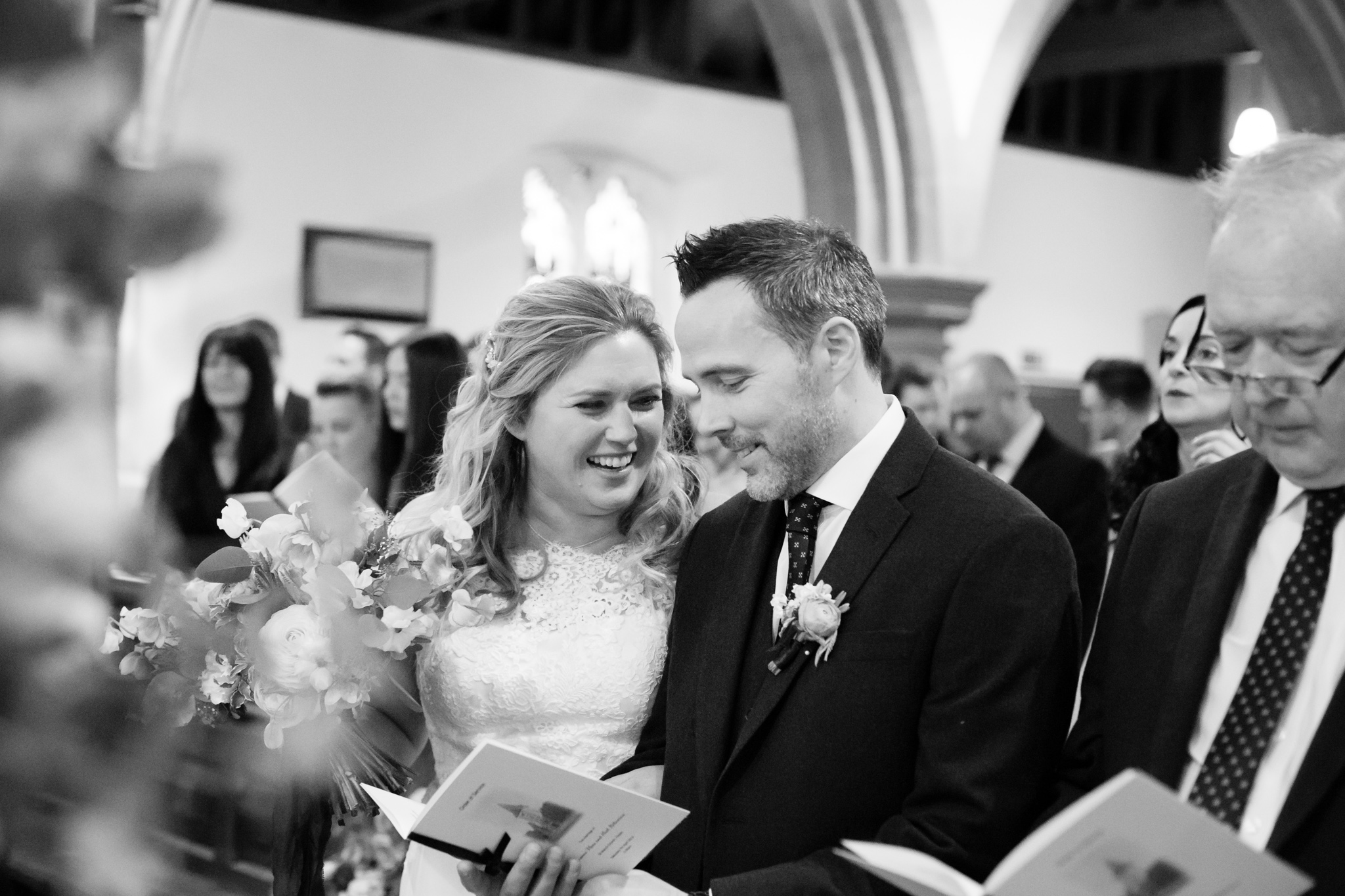 Bride whispering to groom in St Mary the Virgin Church in Hayes near Bromley, Kent