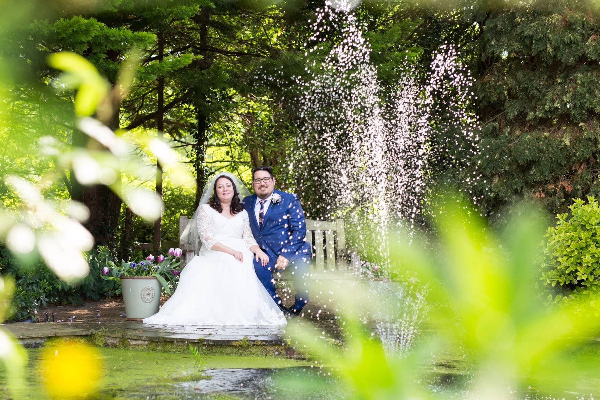 Wedding couple sat on bench outside at Oaks Farm Weddings, Shirley Croydon