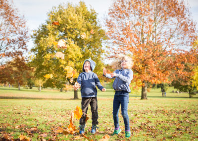 Siblings playing with leaves in Autumn in Beckenham photoshoot.
