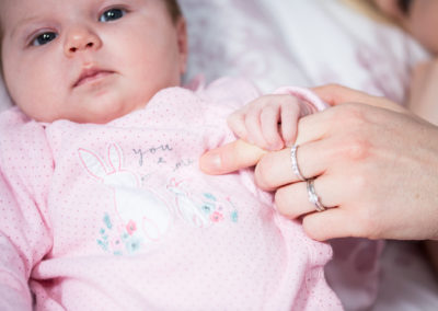 Newborn holding mums fingers taken by Bromley newborn photographer