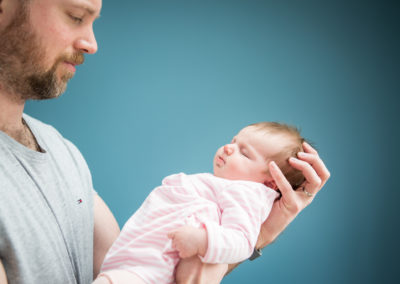 Dad cradling baby daughter in newborn photoshoot in Bromley