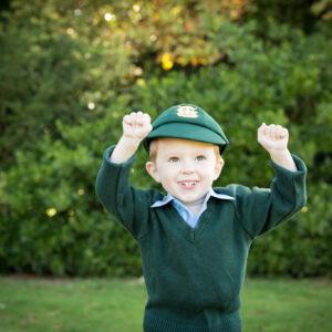 boy in school hat and uniform outside in park