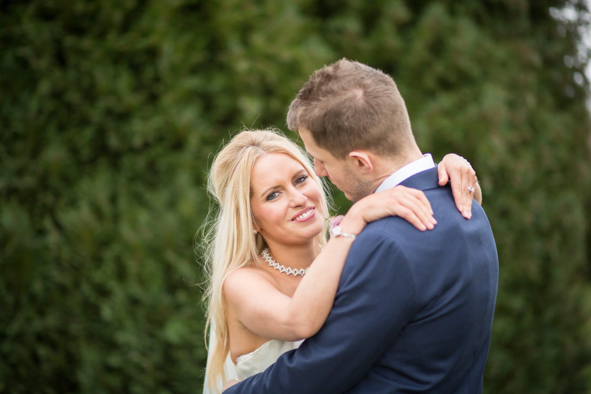 Bride cuddling groom and looking over shoulder in wedding photoshoot in Bromley, Kent