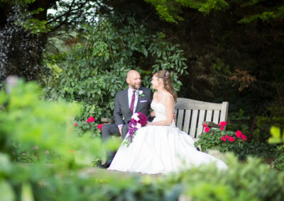 newly married couple sat on bench at Oaks Farm Weddings - taken by Tessa Clements Photography