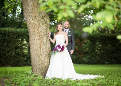 Couple posing by tree at Oaks Farm Wedding venue